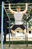 Muscular man doing pull-ups exercise outdoors. Stock Photos