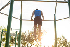 Muscular man doing pull-ups on horizontal bar, training of strongman on outdoor park gym in the morning. Stock Image