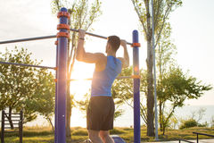 Muscular man doing pull-ups on horizontal bar, training of strongman on outdoor park gym in the morning. Stock Photography