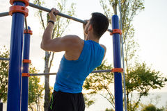 Muscular man doing pull-ups on horizontal bar, training of strongman on outdoor park gym in the morning. Stock Photo