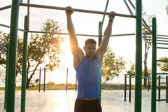Muscular man doing pull-ups on horizontal bar, training of strongman on outdoor park gym in the morning. Stock Images