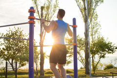 Muscular man doing pull-ups on horizontal bar, training of strongman on outdoor park gym in the morning. Royalty Free Stock Image