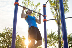 Muscular man doing pull-ups on horizontal bar, training of strongman on outdoor park gym in the morning. Stock Photos
