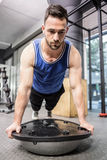 Muscular man doing push up on bosu ball. At the crossfit gym Stock Photos