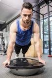 Muscular man doing push up on bosu ball Stock Photos