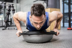 Muscular man doing push up on bosu ball Stock Images