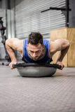 Muscular man doing push up on bosu ball. At the crossfit gym Royalty Free Stock Images
