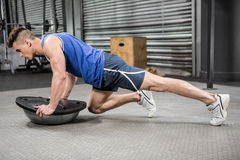 Muscular man doing push up on bosu ball. At the crossfit gym Royalty Free Stock Photos