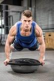 Muscular man doing push up on bosu ball Royalty Free Stock Photo