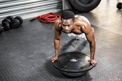 Muscular man doing push up on bosu ball. At the crossfit gym Stock Photography