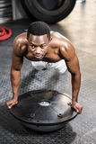 Muscular man doing push up on bosu ball. At the crossfit gym Stock Images