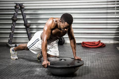 Muscular man doing push up on bosu ball. At the crossfit gym Royalty Free Stock Photography