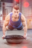 Muscular man doing push up on bosu ball. At crossfit gym Stock Photo