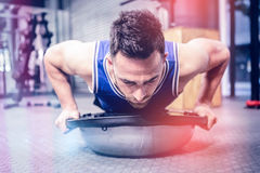 Muscular man doing push up on bosu ball. At crossfit gym royalty free stock images