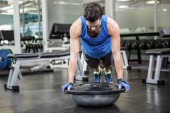 Muscular man doing push up with bosu ball. At the gym Stock Photography