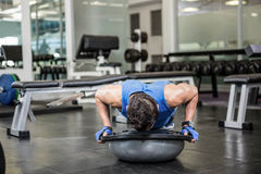Muscular man doing push up with bosu ball. At the gym Stock Image