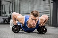 Muscular man doing push up with dumbbells Stock Photos
