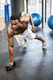 Muscular man doing push up with dumbbells. At the crossfit gym Royalty Free Stock Photos