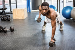 Muscular man doing push up with dumbbells. At the crossfit gym Royalty Free Stock Images