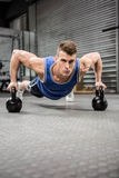 Muscular man doing push up with kettlebells royalty free stock photo
