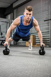 Muscular man doing push up with kettlebells. At the crossfit gym Royalty Free Stock Photo