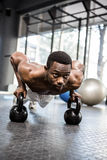 Muscular man doing push up with kettlebells. At the crossfit gym Stock Image