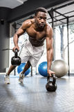 Muscular man doing push up with kettlebells. At the crossfit gym Stock Images