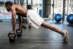 Muscular man doing push up with kettlebells Royalty Free Stock Image