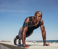 Muscular man doing push ups against blue sky Royalty Free Stock Photos