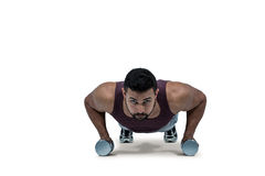 Muscular man doing push ups with dumbbells Stock Image