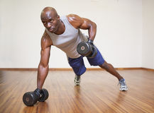 Muscular man doing push ups with dumbbells in gym Royalty Free Stock Photos