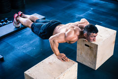 Muscular man doing push ups on fit box Stock Photography
