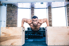Muscular man doing push ups on fit box Stock Photos