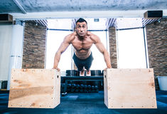 Muscular man doing push ups on fit box Stock Images