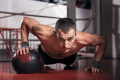 Muscular man doing push-ups with fitness ball Stock Photo