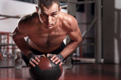 Muscular man doing push-ups with fitness ball Royalty Free Stock Photos