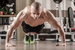Muscular man doing push ups Stock Image