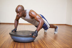 Muscular man doing push ups in gym Royalty Free Stock Images