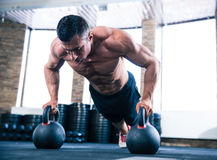 Muscular man doing push ups in gym. Handsome muscular man doing push ups on kettle ball in crossfit gym royalty free stock photo