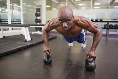 Muscular man doing push ups in gym Stock Photos