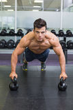 Muscular man doing push ups with kettle bells in gym Stock Photos