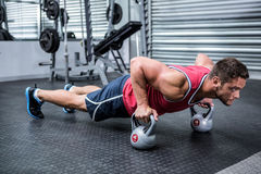 Muscular man doing push-ups with kettlebells Royalty Free Stock Image