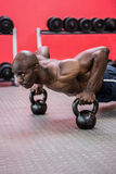 Muscular man doing push-ups with kettlebells Royalty Free Stock Photos