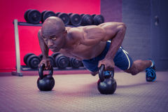 Muscular man doing push-ups with kettlebells Stock Images