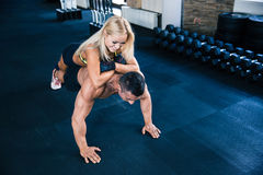 Muscular man doing push ups with woman on back Stock Images