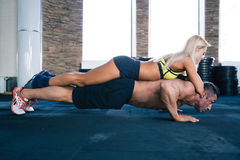 Muscular man doing push ups with woman on back. Handsome muscular men doing push ups with women on back at gym stock photo
