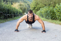 Muscular man doing pushup in the park. Royalty Free Stock Photo