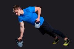 Muscular man doing pushups while pulling Stock Photos
