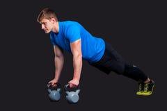 Muscular man doing pushups while pulling Royalty Free Stock Photo