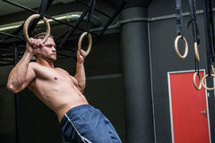 Muscular man doing ring gymnastics Stock Images